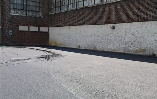Paved parking area by brick building