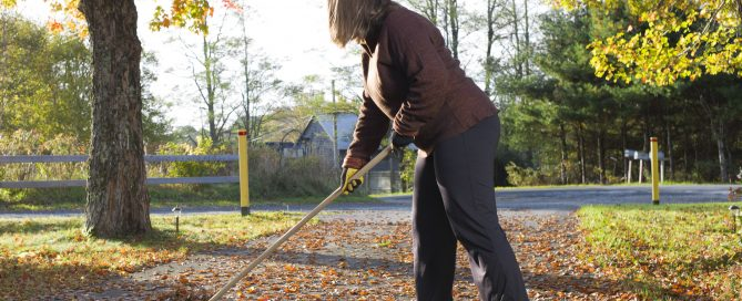 Woman sweeping fall leaves